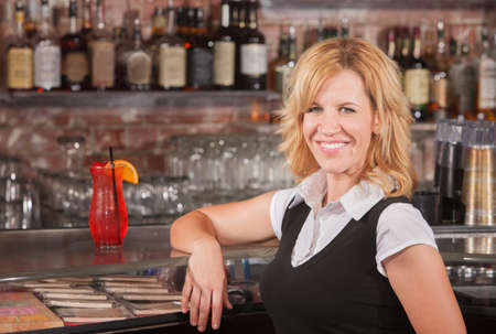 Pretty blond mature woman with arm on counter at bar Stock Photo - 17591164