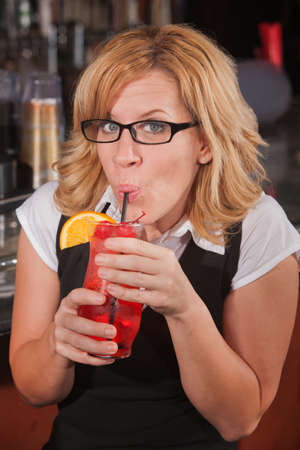 Mature blond female sipping drink with a straw Stock Photo - 17591140