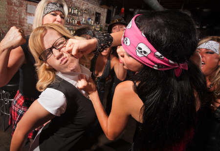 women fighting: Female nerd with eyeglasses punched in fight with gang