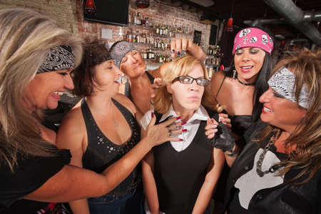 teasing: Female motorcycle gang touching a frightened nerd Stock Photo