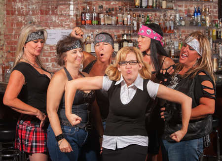 puckering lips: Female motorcycle gang laughing at nerd in bar Stock Photo