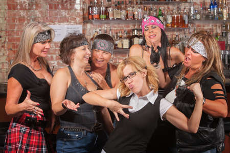 wimp: Nerd flexes muscles for tough female gang in bar Stock Photo
