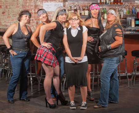 is embarrassed: Nervous nerd lady in between gang of tough women in bar