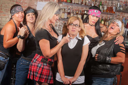 Scared young woman with group of big female biker gang members photo