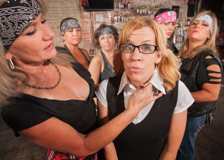 Tough biker gang woman with hand near female nerd's neck photo