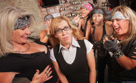 Frightened blond nerd laughed at by gang of women photo