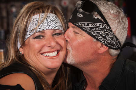 Smiling woman in bandanna being kissed by handsome mature man photo