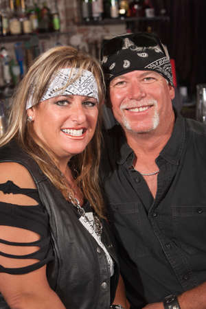 Handsome middle aged couple in leather and bandanna in bar photo