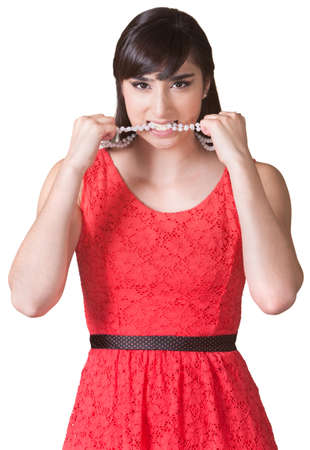 Angry young woman biting her pearl necklace photo