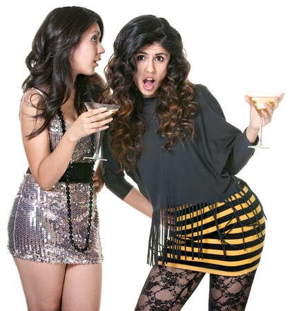 minifalda: Chica del club sorprendido de escuchar a un amigo diciéndole secretos Foto de archivo