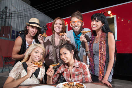 Six smiling mixed people holding pizza slices in front of food truck Stock Photo - 18123465