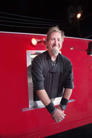 Smiling handsome chef sticking out of restaurant truck Stock Photo - 18123464
