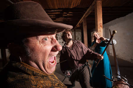 swashbuckler: Angry swordsman dueling with European male indoors Stock Photo