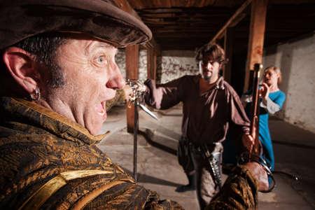 berserk: Berserk swordsman attacking man and woman indoors