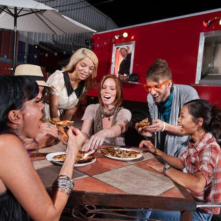 Groep van lachende mensen die pizza eten bij een food truck