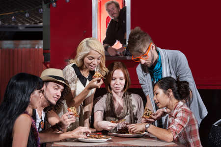 Mixed group of hipsters with pizza at food truck photo