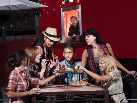 Group of Hipsters eating pizza at a mobile cafe photo