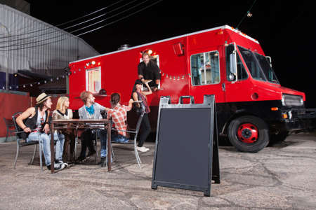 truck: Happy diners at food truck with blank sign