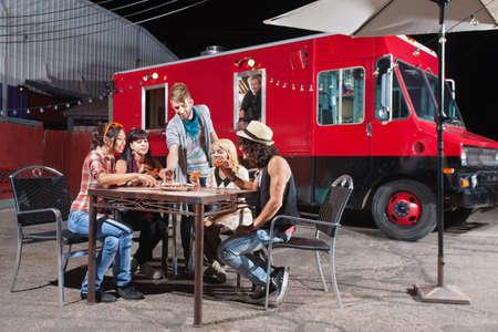 Chef-kok kijkt tevreden klanten aandeel pizza bestellingen van voedsel truck Stockfoto