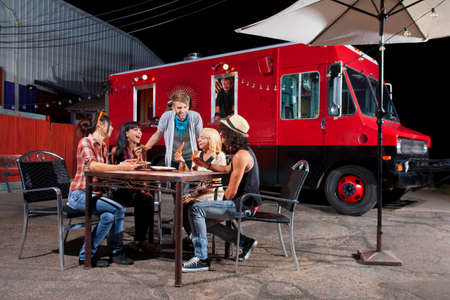 dining out: Laughing friends at food truck eating pizza slices Stock Photo