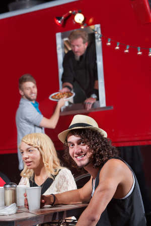 Caucasian male at table with friends ordering pizza photo
