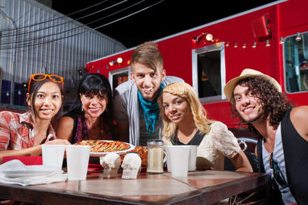 dining out: Group of five adults smiling at table near mobile cafe