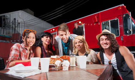 Smiling patrons at table in front of chef and food truck photo