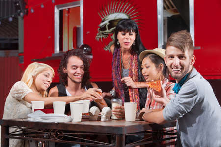 Smiling hipster with lip piercing eating pizza with friends outside Stock Photo - 18299687