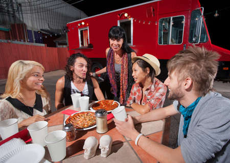 Five hipsters at mobile pizza restaurant with plates of food photo