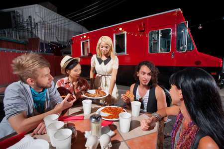 People in conversation while eating pizza from food truck photo