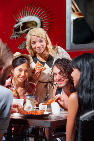 dining out: Mixed group of happy people eating pizza outside Stock Photo