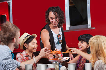 Happy group of people sharing slices of pizza photo