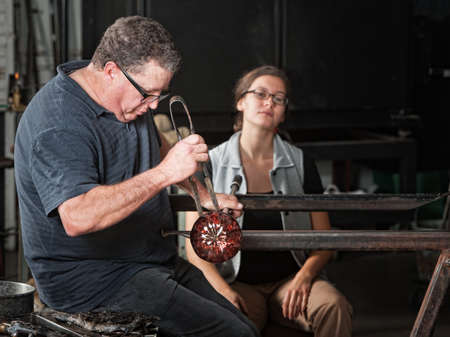 Student watching European glass artisan work on a round vase photo