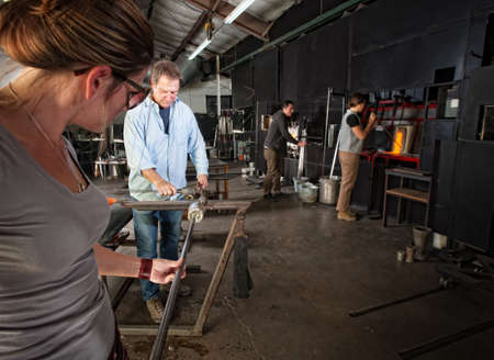 Four men and women busy in a glass making workshop