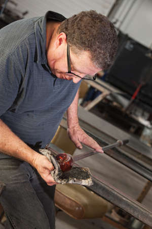 Artist rolling hot glass object with mitts on workbench photo