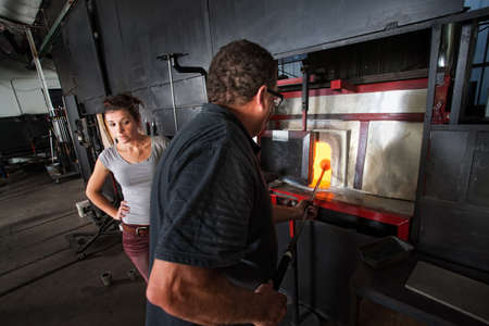 Two glass artists putting object in hot kiln photo