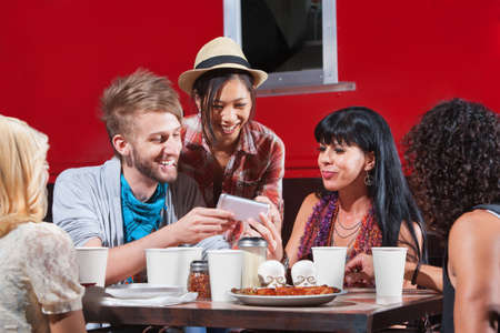 Group of diverse people laughing with phone and eating pizza photo