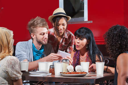 Group of friends eating out and looking at smartphone Stock Photo - 18606968