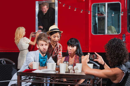 Friends sticking out tongues for photo near food truck photo