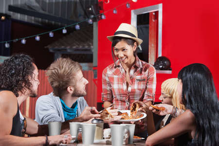 Smiling Asian woman sharing pizza slices with friends at food truck Stock Photo - 18607018