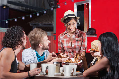 Cute Asian woman serving pizza to diners outside Stock Photo - 18607075