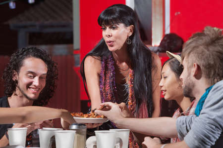 Cute mature woman sharing pizza with young group Stock Photo - 18607072