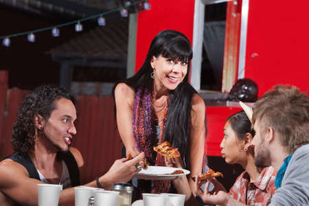 Group of four happy people eating pizza outside Stock Photo - 18607021