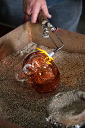 Blowtorch finishing fine art glass object in frit Stock Photo - 18567212