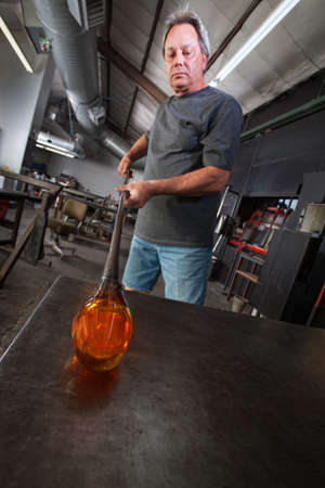 Serious worker with molten glass object on workbench Stock Photo - 18607070