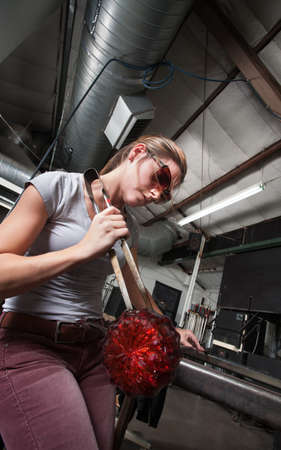 Serious Caucasian artist with tongs and decorative glass object Stock Photo - 18607195