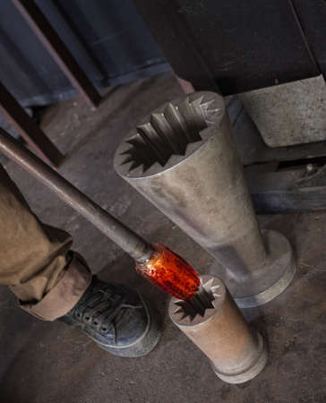 tool and die: Hot glass art object pulled out of iron die Stock Photo
