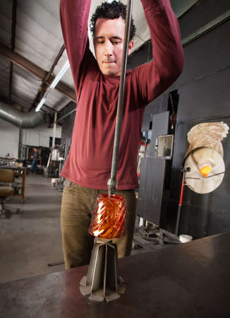 Young industrial artist pulling hot glass from iron die photo