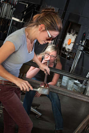Team of pretty female glass artists finishing vase object photo