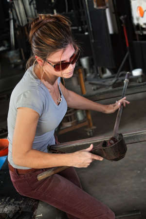 Female glass manufacturing business artist working with tools photo
